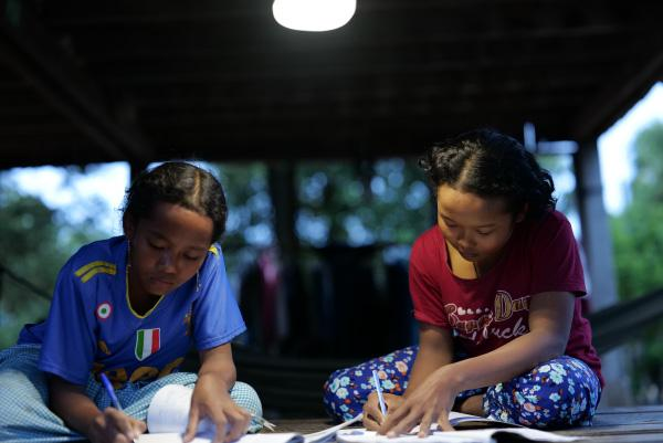 photo: Children studying under the light of a solar lantern. They told us they dream of continuing in school and someday taking up a profession.