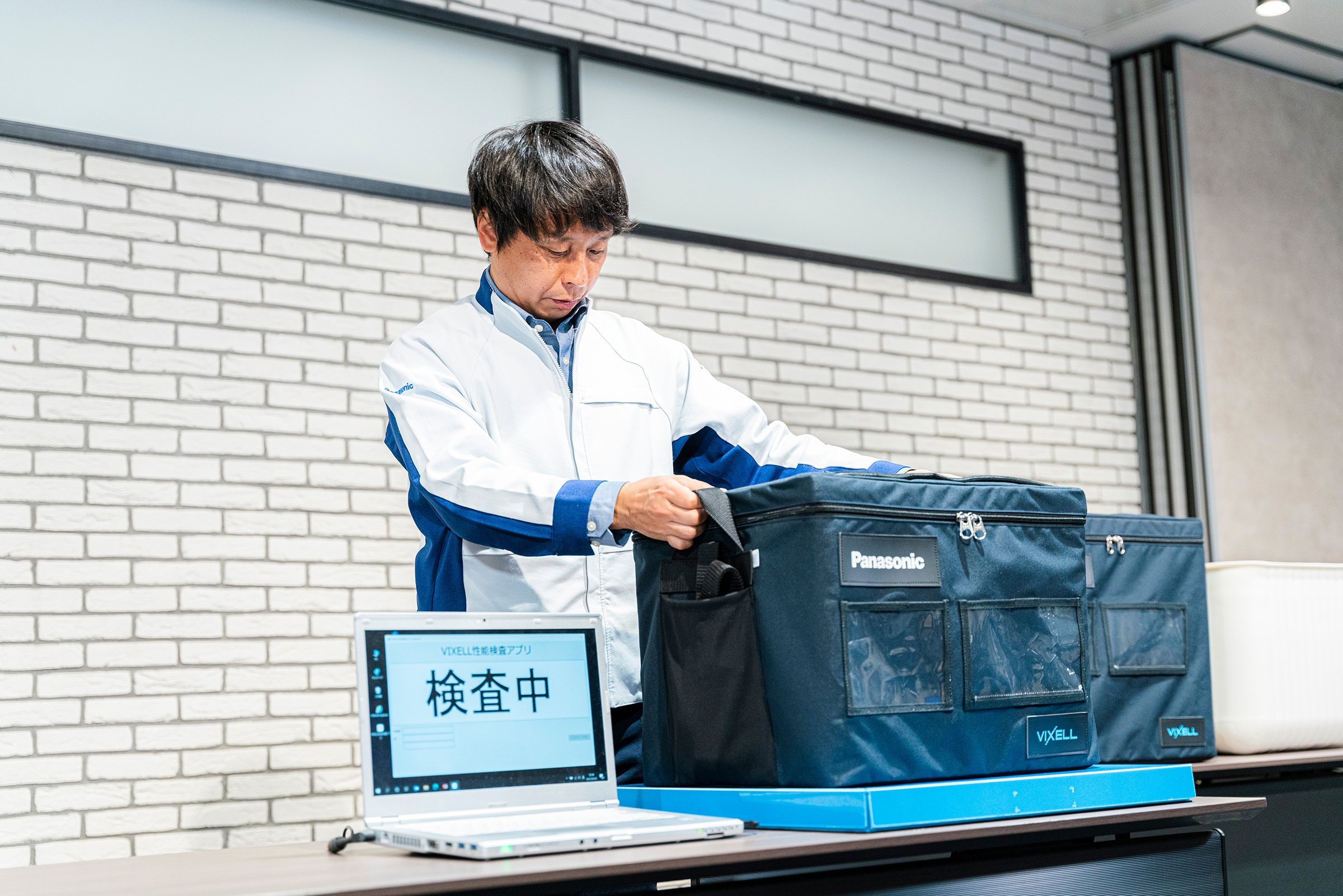 Photo: Hideji Kawarazaki, Manager, Engineering Division demonstrating remote monitoring of the internal condition of a cooling box using the powered inspection stand.