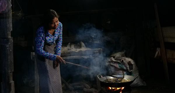 photo: A woman making banana chips for sales. Using the solar lantern enables her to work in the early hours when it is still dark, and she says her income has increased as a result.