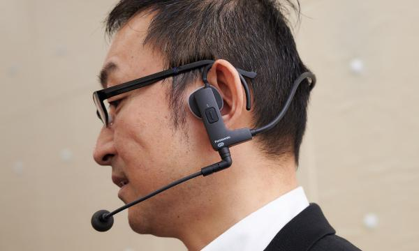 photo: The bone conduction headset worn for actual work. The earhook can be turned to adjust the fit to the size of the user's head.