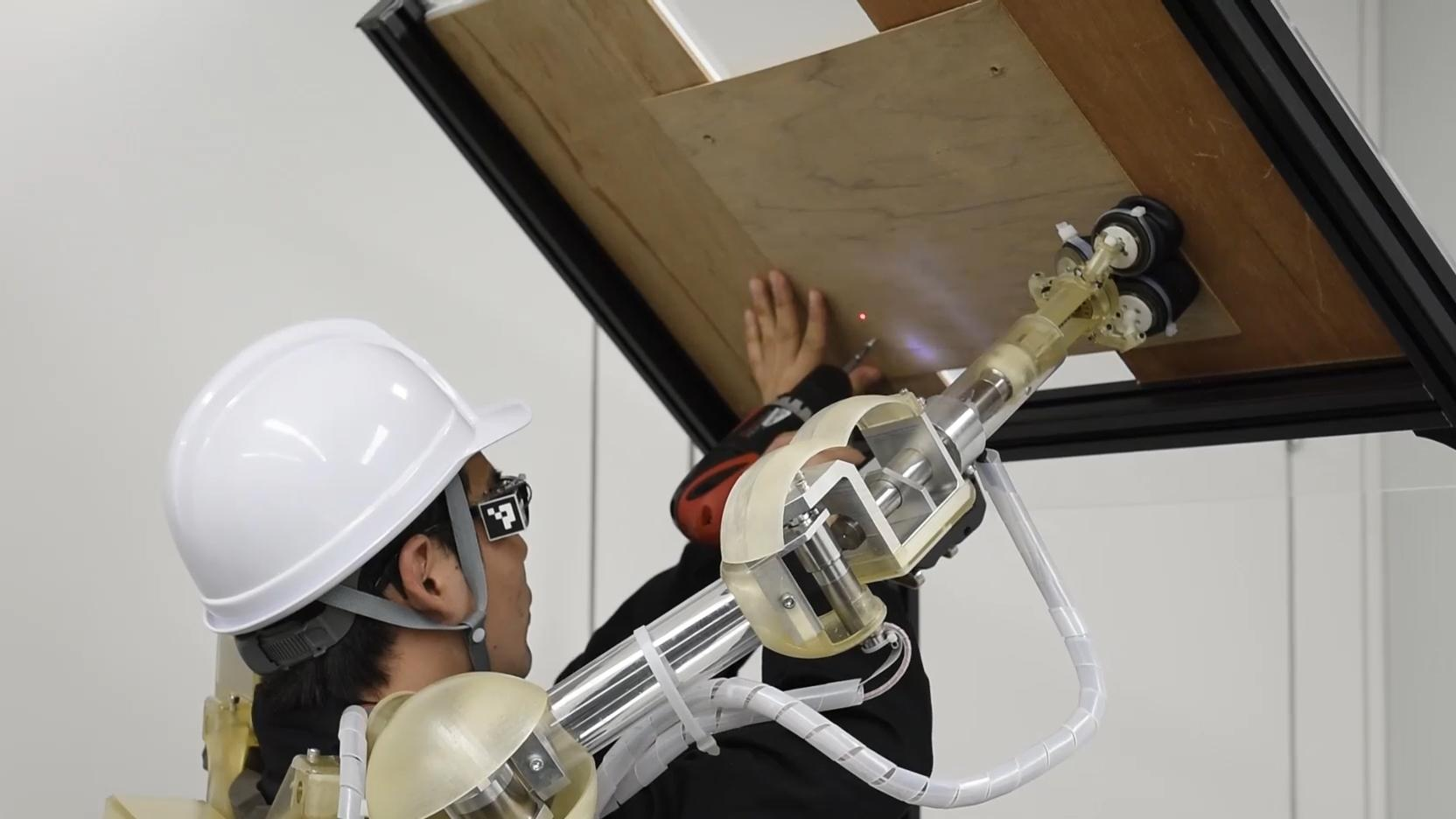 Photo: The demonstration of the 3rd Arm by holding in place and screwing in a ceiling panel