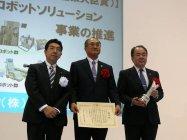 表彰状とトロフィーを授与された野村常務役員(中央)と山根院長(右)