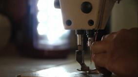 コミュニティファクトリーで働く女性の手元を照らすソーラーランタン