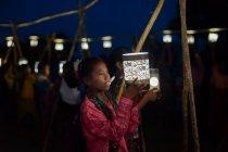 ランタンの明かりとともに浮かび上がった動物を見つめる子ども。