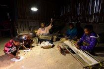 ソーラーランタンの明かりの下、仕事や勉強に取り組む家族。