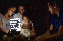 ソーラーランタンの明かりとシェードに描かれたパナソニック従業員のメッセージを見つめる家族