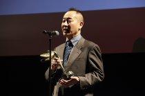 授賞式でトロフィーを手に挨拶する、本作品を手がけたパナソニック株式会社 小島 勝 主幹