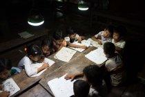 パナソニックの「ソーラーランタン」を使って勉強する子どもたち