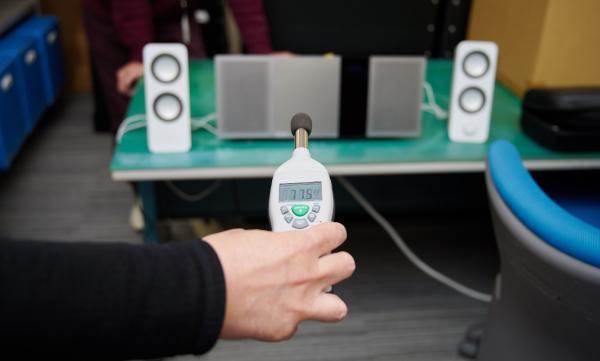 写真:地下鉄の走行中の列車内の騒音環境を実験室で再現し、通話のしやすさを検証