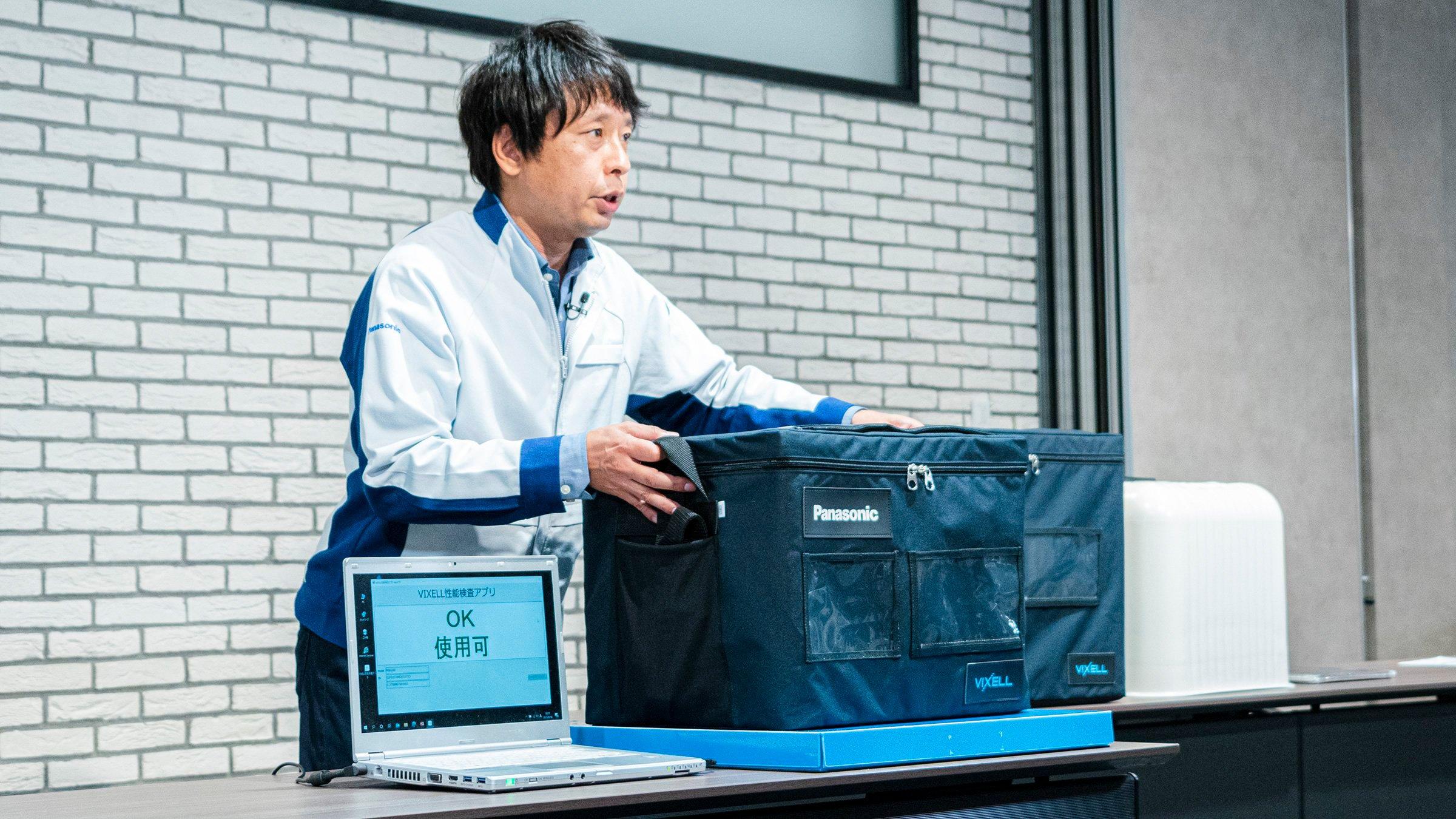 写真:専用の検査台(「VIXELL」下の青い台)に乗せると、非接触給電技術によりワイヤレスで真空度の確認が可能に